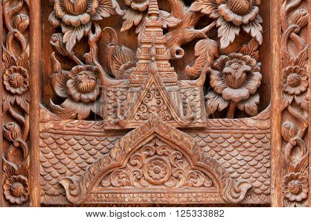 Silhouette of a roof of a Buddhist temple in the tradition of northern Thailand. Carved on a wooden door of Buddhist temple in Chiang Mai Thailand.