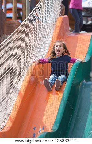 Adorable screaming girl on bright chute at playground