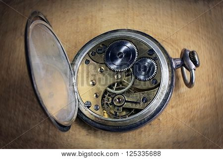 Pocket watch inside on wooden desk with wheels and springs golden color