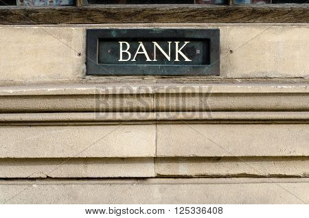 Bank sign painted on letterbox in wall. White word Bank painted on metal letterbox or deposit box in a stone wall in Bath Somerset UK
