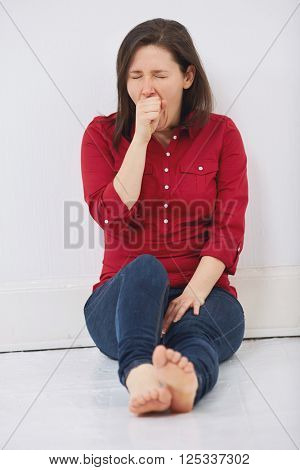 Young woman yawning while sitting on white wooden floor against white wall