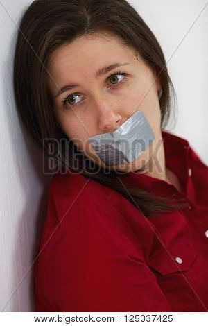 Young woman with her lips being taped over with silver tape