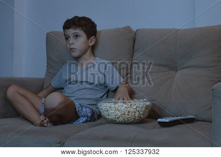 Small Boy On The Couch Watching Tv And Eating Popcorn At Night In The Living Room