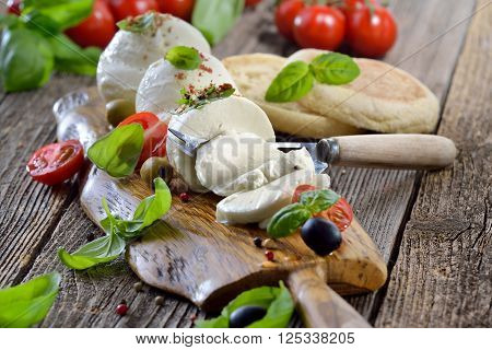 Italian mozzarella cheese snack with cherry tomatoes, basil and olives served on a wooden board with toast bread