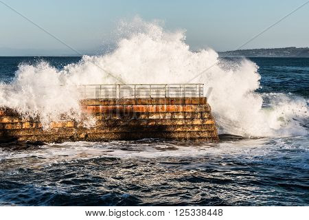 Dramatic wave crashing over seawall at the La Jolla Children's pool.