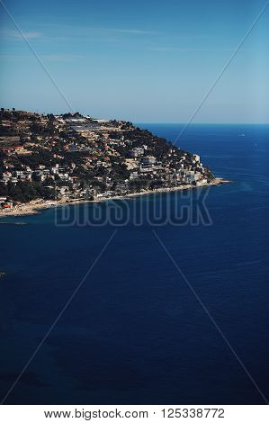 coastline cape green hilly sea shore with residential buildings against clear blue sky on summer day time on seascape background ** Note: Soft Focus at 100%, best at smaller sizes