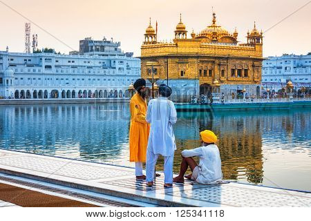 AMRITSAR, INDIA - AUGUST 26, 2011: Sikh guard talking with devotees in Golden Temple Sri Harmandir Sahib Gurdwara in Amritsar, Punjab, India.  Golden Temple is the holiest Gurdwara of Sikhism