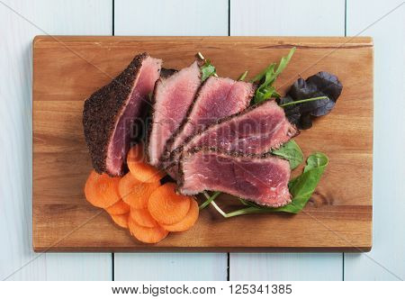 Rare pepper steak with carrot and rocket salad on wooden board