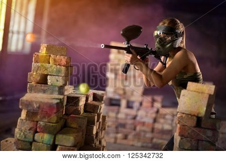 Paintball player in mid game defending the fortification