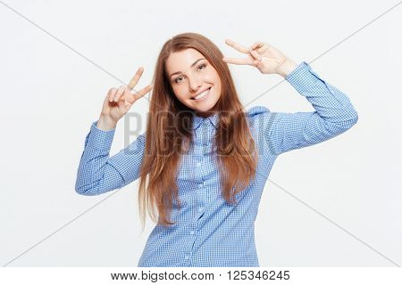 Smiling casual woman showing two fingers sign isolated on a white background