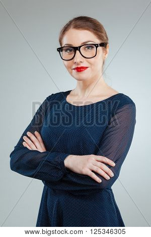 Happy beautiful woman with arms folded standing isolated on a white background and looking at camera