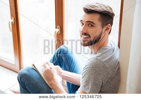 Happy bearded young man sitting on window sill and writing in notebook