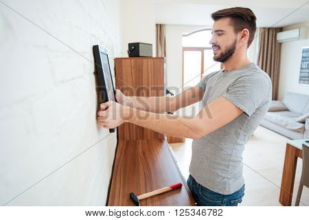 Concentrated handsome young man standing and hanging picture on white wall in the room