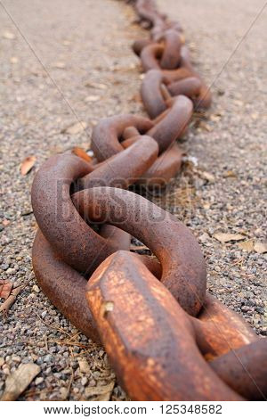 Large Rusted Metal Chains (large rusted metal chains sprawled against gravel).