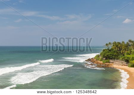 travel, tourism, vacation, seascape and summer holidays concept - sea or ocean waves and blue sky on Sri Lanka beach