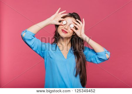 Funny happy young woman holding round white candies in front of her eyes over pink background