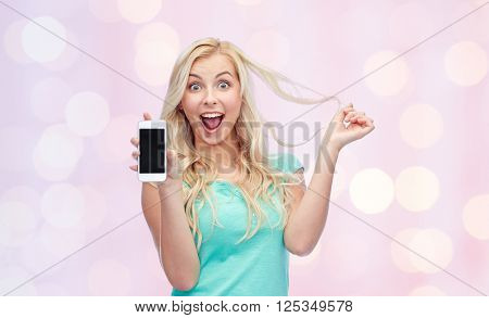 emotions, expressions, technology and people concept - smiling young woman or teenage girl showing blank smartphone screen over pink holidays lights background