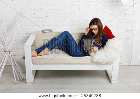 Teenager girl relax home, sitting on sofa with tablet computer. Child wears glasses, eyeglasses. Girl in eyewear with gadget tablet lying on sofa. Adolescence, internet addiction. High key