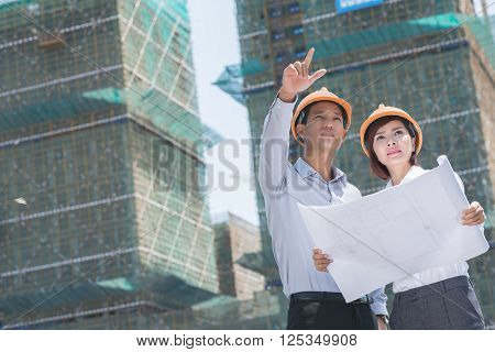 Young Vietnamese engineers comparing blueprint with actual building