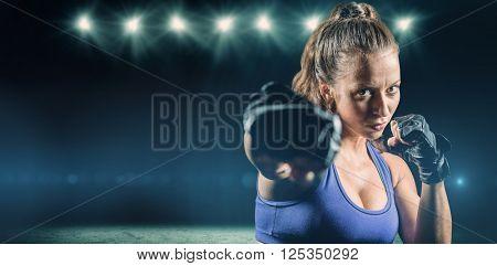 Portrait of female fighter punching against desert landscape