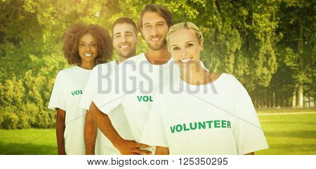Smiling volunteer group against trees and meadow