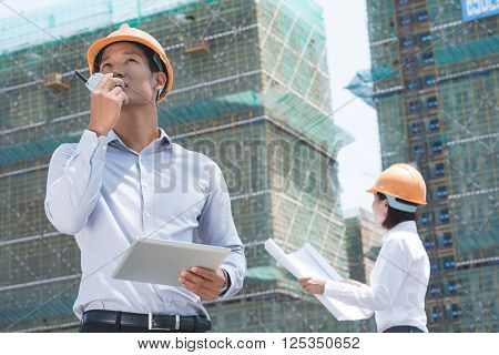 Vietnamese supervisor with digital tablet using walkie-talkie at construction site