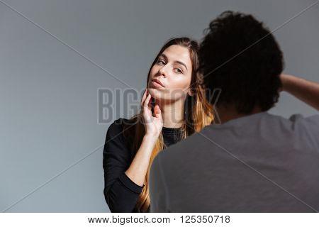 Man photographing female model in studio