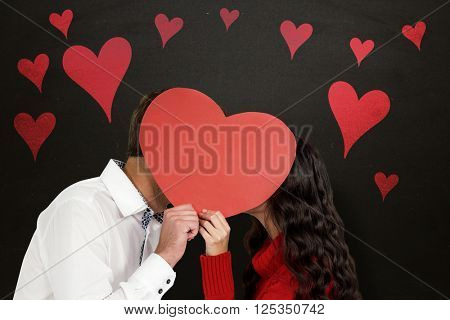 Couple covering faces with paper heart against blackboard
