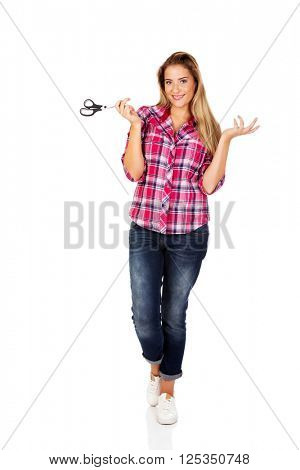 Young woman holding scissors and gesturing dont know