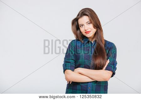Beautiful smiling young woman with long hair in checkered shirt standing with arms crossed over white background
