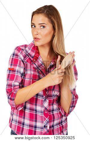 Young woman combing hair hairbrush