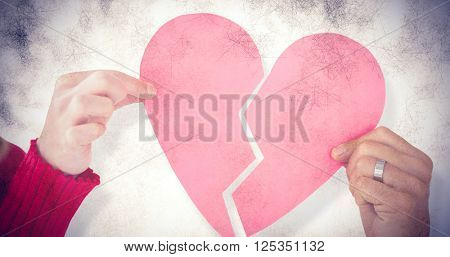 Couple holding two halves of broken heart against grey background