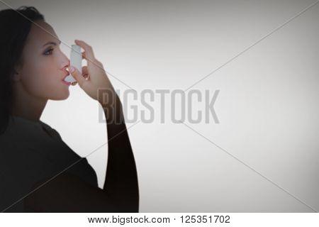 Asthmatic brunette using her inhaler against grey vignette