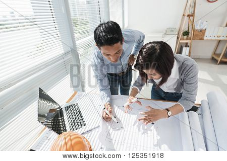 Two Vietnamese colleagues working in architect bureau