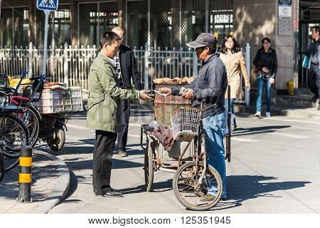 Beijing China - October 15 2013: Street vendor selling potatoes to a customer in Beijing China.
