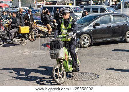 Beijing China - October 15 2013: Chinese policeman patrol on motor scooters on a busy street in Beijing China.