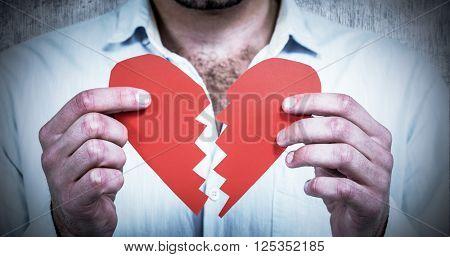 Sad man holding heart halves against grey background