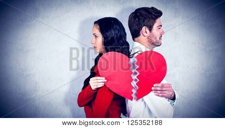 Couple back to back holding heart halves against white background