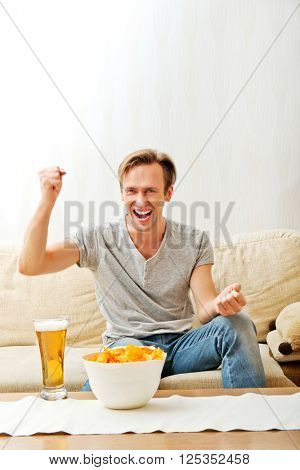 Angry man screaming while watching sports on tv