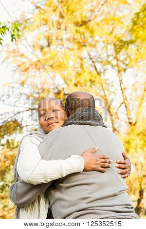 Peaceful happy senior couple embracing in parkland
