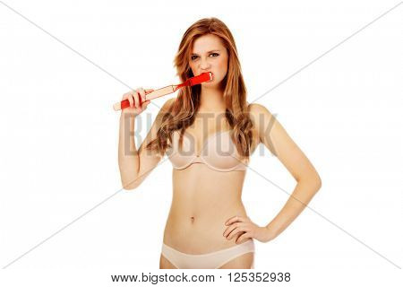 Woman brushing her teeth with huge toothbrush