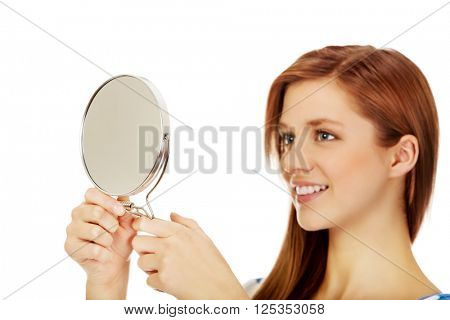 Teenage beautiful woman looking in a mirror