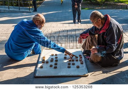 Beijing China - October 15 2013: Elderly Chinese men playing Chinese chess called Xiangqi in a park outside the Temple of Heaven Beijing China. It is a very popular in China strategy board game for two players.