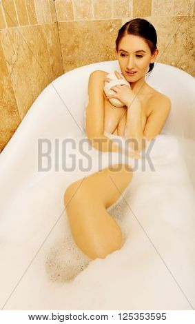 Woman washing herself by sponge