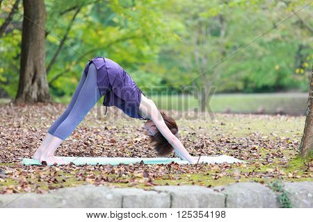Japanese woman outside doing yoga Downward-Facing Dog