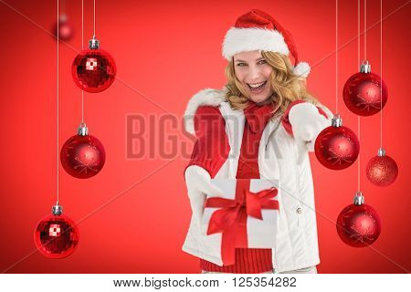 Festive blonde holding christmas gift and pointing her finger against red vignette