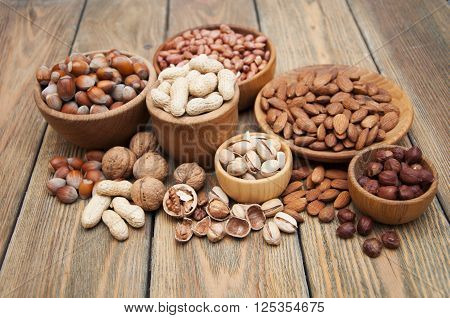 Variety of nuts: walnut hazelnut hazelnuts peanuts pine nuts and other on a wooden background