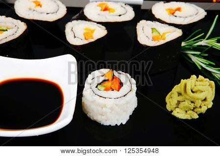 Roll with Cucumber , Cream Cheese with raw Tuna and Salmon inside. on black wooden plate. Japanese traditional Cuisine