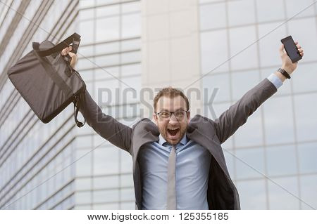 Manager celebrating the end of working hours on Friday with his hands up in front of the business building. Weekend is about to start.