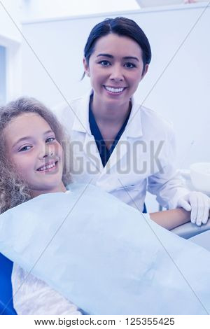 Little girl smiling with her pediatric dentist at the dental clinic